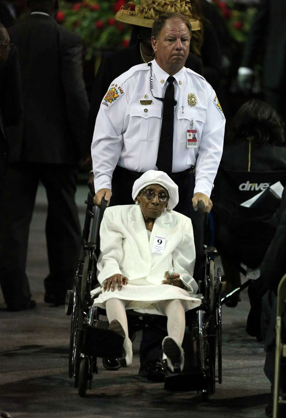 A woman is assisted into the arena before the funeral service for Sen. Clementa Pinckney, Friday, June 26, 2015, in Charleston, S.C. President Barack Obama will deliver the eulogy at Pinckney's funeral Friday at College of Charleston's TD Arena near the Emanuel AME Church, the scene of last week's shooting. (Grace Beahm/The Post And Courier via AP)