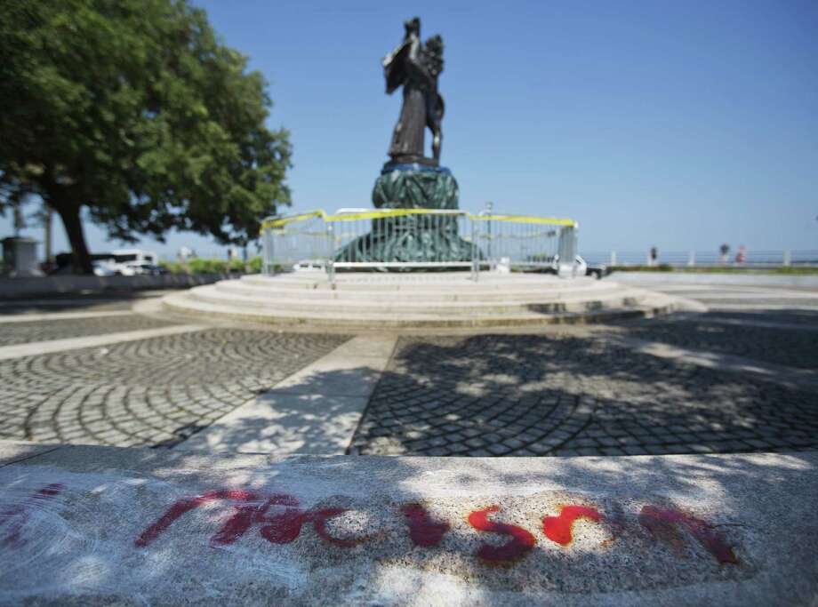 "FILE - In this June 21, 2015, file photo, the word ""racism"" is painted next to a statue memorializing the Confederacy with it's tarp-covered base that was spray painted with ""Black lives matter"" in Charleston, S.C. Confederate monuments in a half-dozen places this week have been defaced _ a telling sign of the racial tension that permeates post-Ferguson America. (AP Photo/David Goldman, File) Photo: AP / AP"