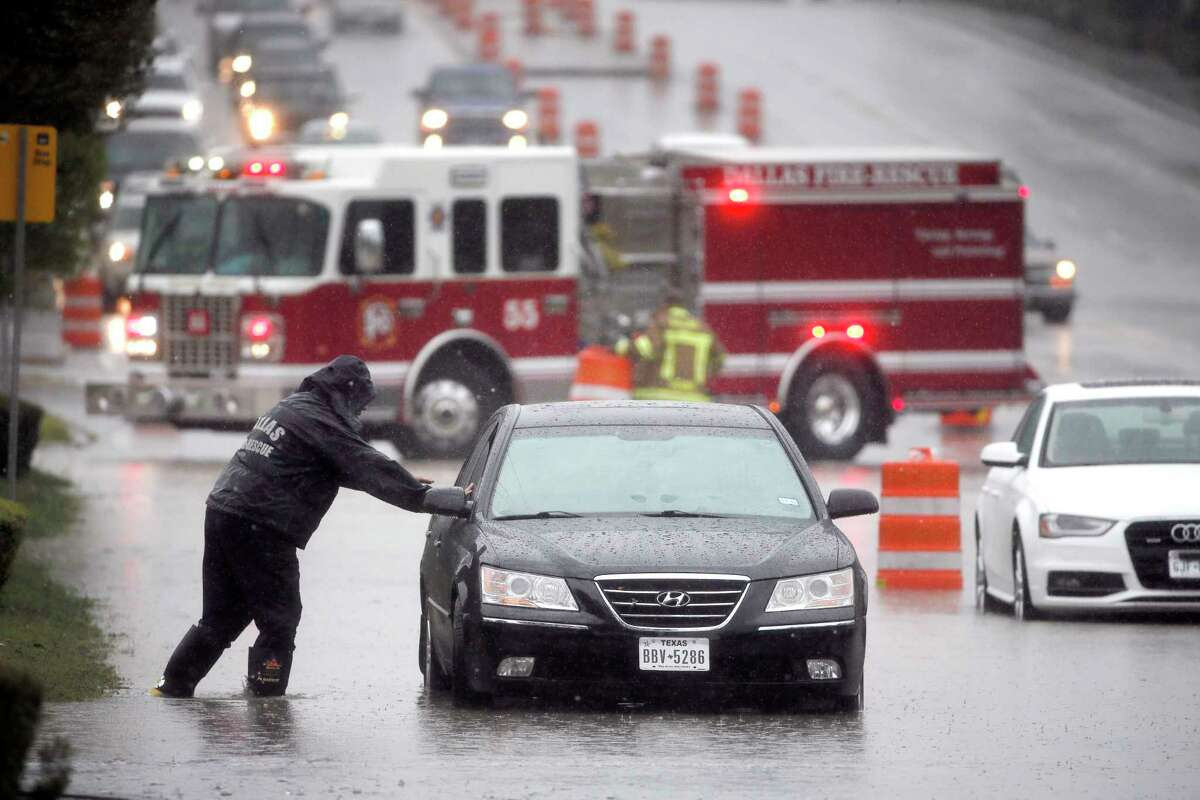 A Dalls Fire Rescue responder makes his way over to a stalled vehicle to check on the drive still inside on Hillcrest Road Friday, Oct. 23, 2015, in Dallas. The vehicle stalled after the road quickly flooded during a heavy rain fall. More rain soaked parts of Texas on Friday as millions of residents braced for other storms that could spin off from massive Hurricane Patricia approaching southwest Mexico.