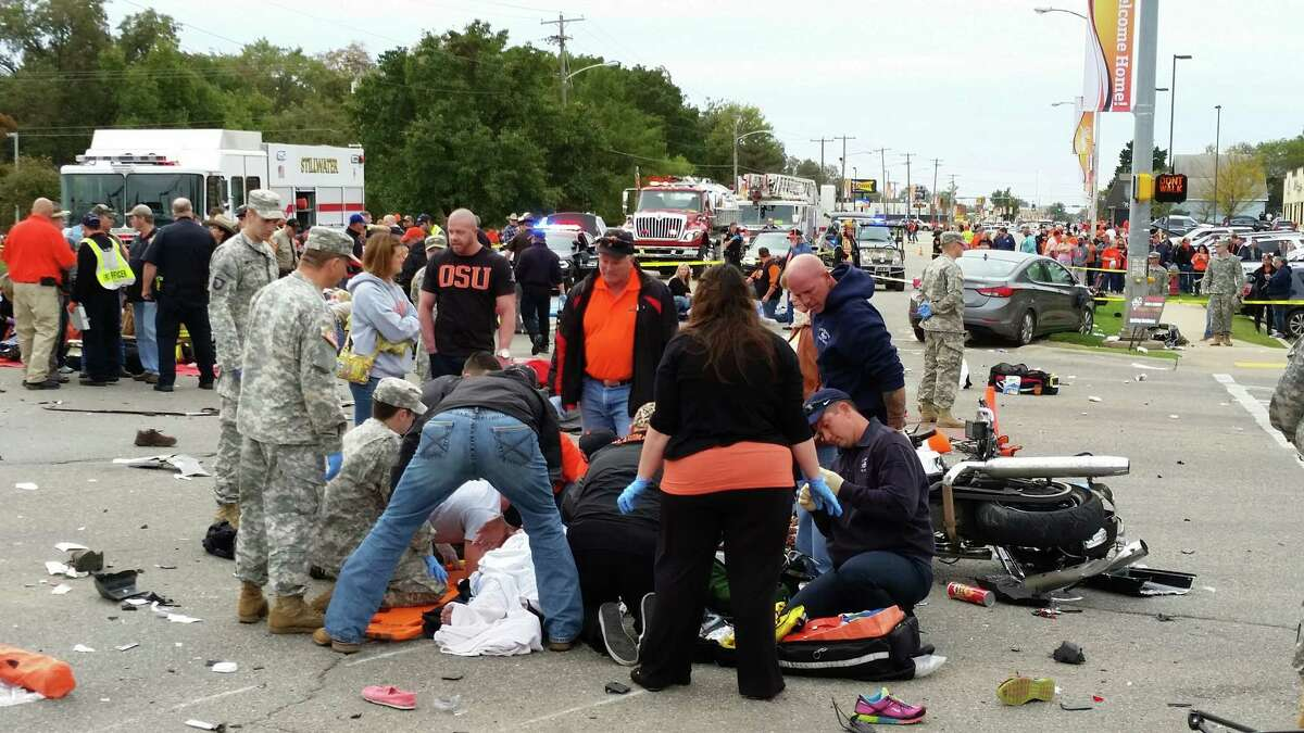 Emergency personnel and spectators respond after a vehicle crashed into a crowd of spectators during the Oklahoma State University homecoming parade, killing three people and causing multiple injuries, on Saturday, Oct. 24, 2015, in Stillwater, Oka.