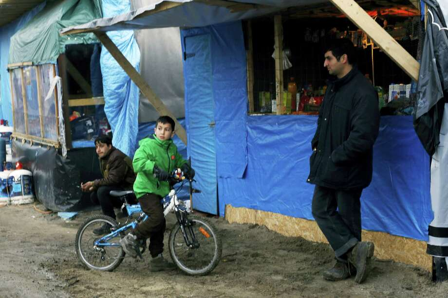 """A child rides his bicycle in a makeshift migrants camp near Calais, France, Thursday Feb. 25, 2016.  A French court has given the green light for the state to evict some hundreds of migrants from their shelter in part of the camp locally referred to as """"the jungle"""". Photo: AP Photo/Jerome Delay   / AP"""