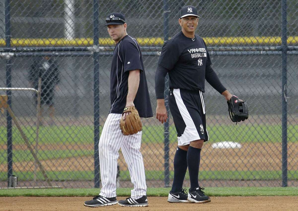 The New York Yankees' Alex Rodriguez, right, walks past Chase Headley during a workout Tuesday at the Yankees minor league facility in Tampa, Fla.
