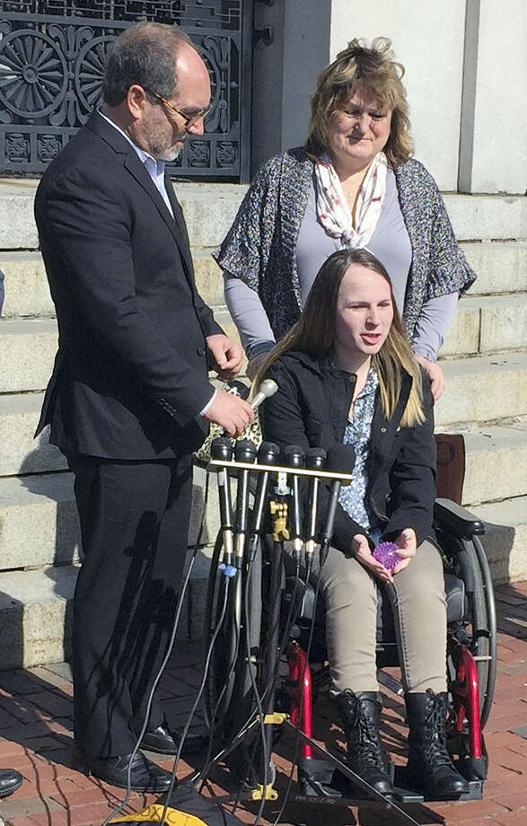 Justina Pelletier, seated, speaks to media alongside the Rev. Patrick Mahoney, left, and her mother Linda Pelletier on Thursday, Feb. 25, 2016, outside the Statehouse in Boston. The Pelletier's filed a lawsuit against Children's Hospital in Boston over a medically-related custody dispute. The case hinged on dueling diagnoses of Justina's condition. Photo: AP Photo/Bob Salsberg / AP