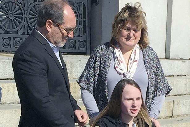 Justina Pelletier, seated, speaks to media alongside the Rev. Patrick Mahoney, left, and her mother Linda Pelletier on Thursday, Feb. 25, 2016, outside the Statehouse in Boston. The Pelletier's filed a lawsuit against Children's Hospital in Boston over a medically-related custody dispute. The case hinged on dueling diagnoses of Justina's condition.