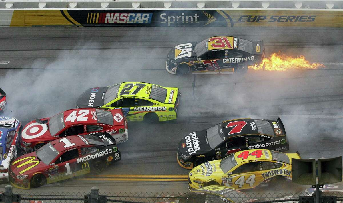 Flames trail from the car of Ryan Newman (31) after a pileup of crashed cars around the track during the NASCAR race at Talladega Superspeedway Sunday in Talladega, Ala.