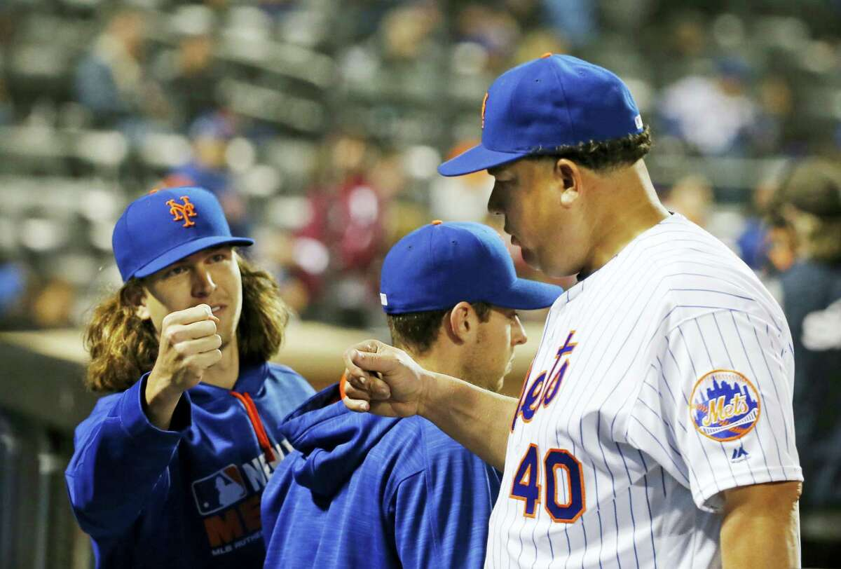 New York Mets starting pitcher Jacob deGrom (48) greets the Mets starting pitcher Bartolo Colon (40) after Colon pitched through eight innings of the Mets 4-1 victory over the Atlanta Braves Monday in New York.