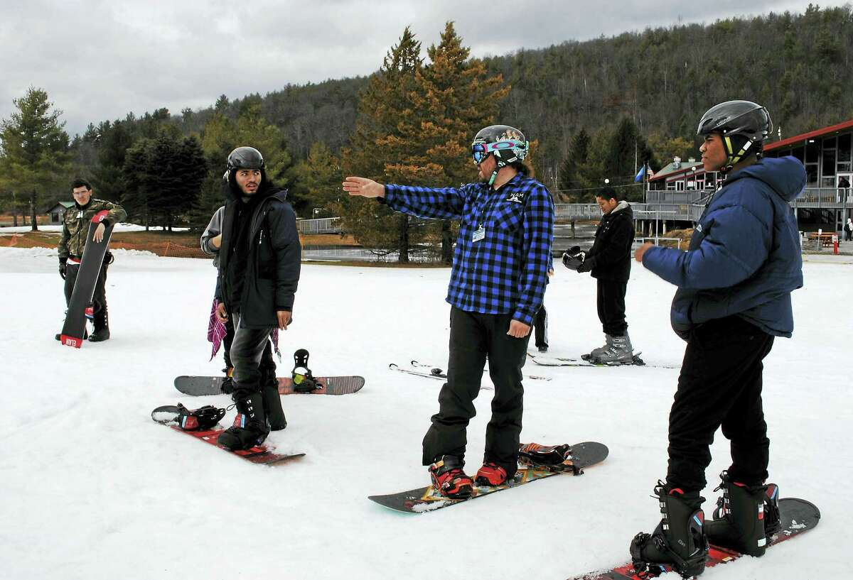 Thirty-seven students in grades 10-12 from the Academy of Engineering and Green Technology in Hartford took to the slopes at Mohawk Mountain in Cornwall on Thursday for free skiing as part of Mohawk's Achieving Excellence Program. Here, the snowboarders receive instructions for how to get onto the ski lift.