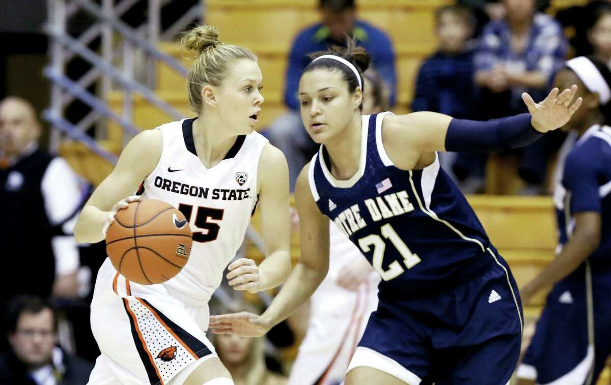 Oregon State guard Jamie Weisner, left, drives on Notre Dame guard Kayla McBride during the first half of an NCAA college basketball game in Corvallis, Ore., Sunday, Dec. 29, 2013. (AP Photo/Don Ryan)