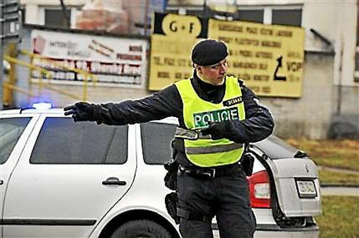 A police officer controls traffic near a restaurant where a gunman opened fire in Uhersky Brod, east of the Czech Republic, Tuesday, Feb. 24, 2015.