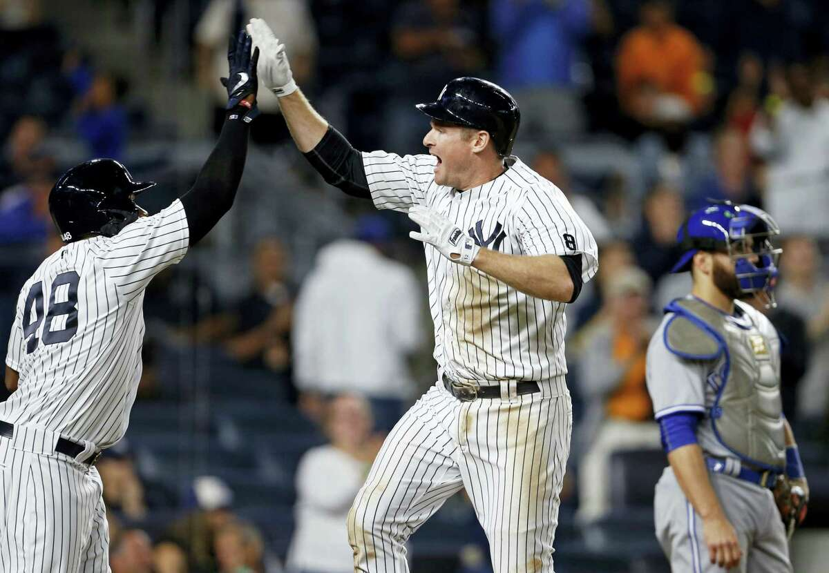 New York'S Chase Headley celebrates hitting a two-run home run with Eric Young Jr. (48) as Toronto catcher Russell Martin looks away during the eighth inning.