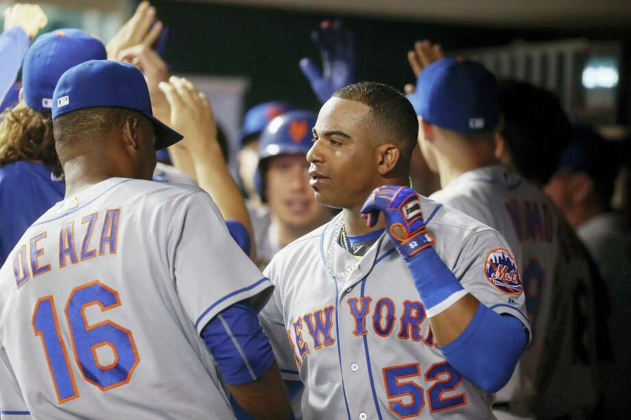 New York's Yoenis Cespedes (52) celebrates in the dugout after hitting a two-run home run off Cincinnati Reds relief pitcher Michael Lorenzen during the seventh inning Tuesday. That blast helped the Mets beta the Reds for the 13th straight time. Photo: JOHN MINCHILLO — THE ASSOCIATED PRESS  / AP