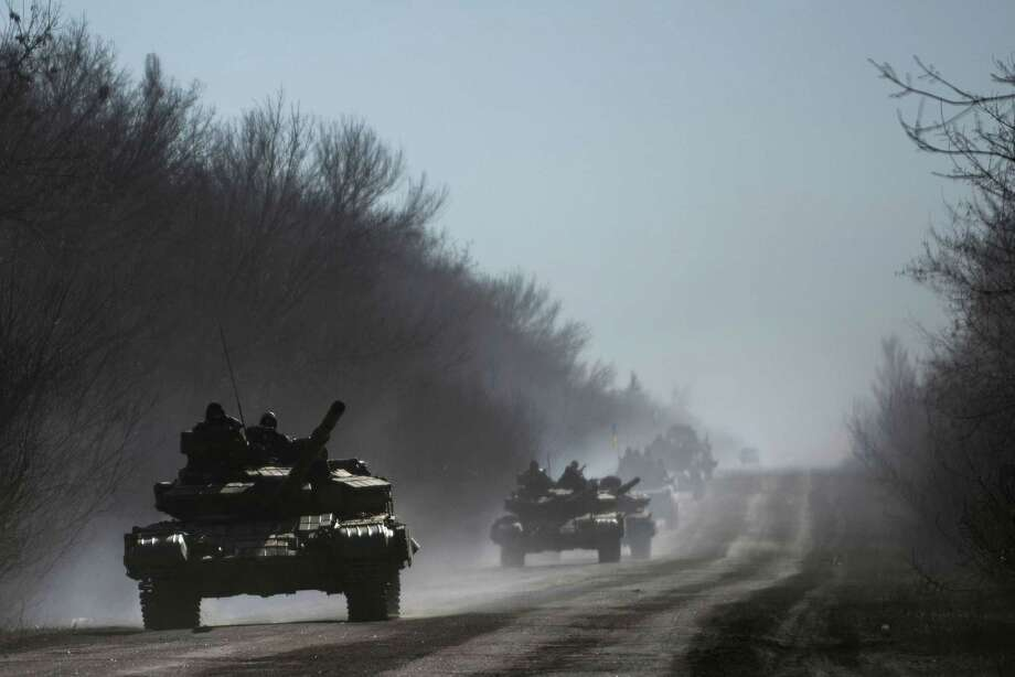 Ukrainian troops ride on tanks near Artemivsk, eastern Ukraine, Tuesday, Feb. 24, 2015. Ukrainian officials said they havenít yet started pulling heavy weapons back from a frontline in eastern Ukraine because of continued rebel violations of a cease-fire deal. (AP Photo/Evgeniy Maloletka) Photo: AP / AP