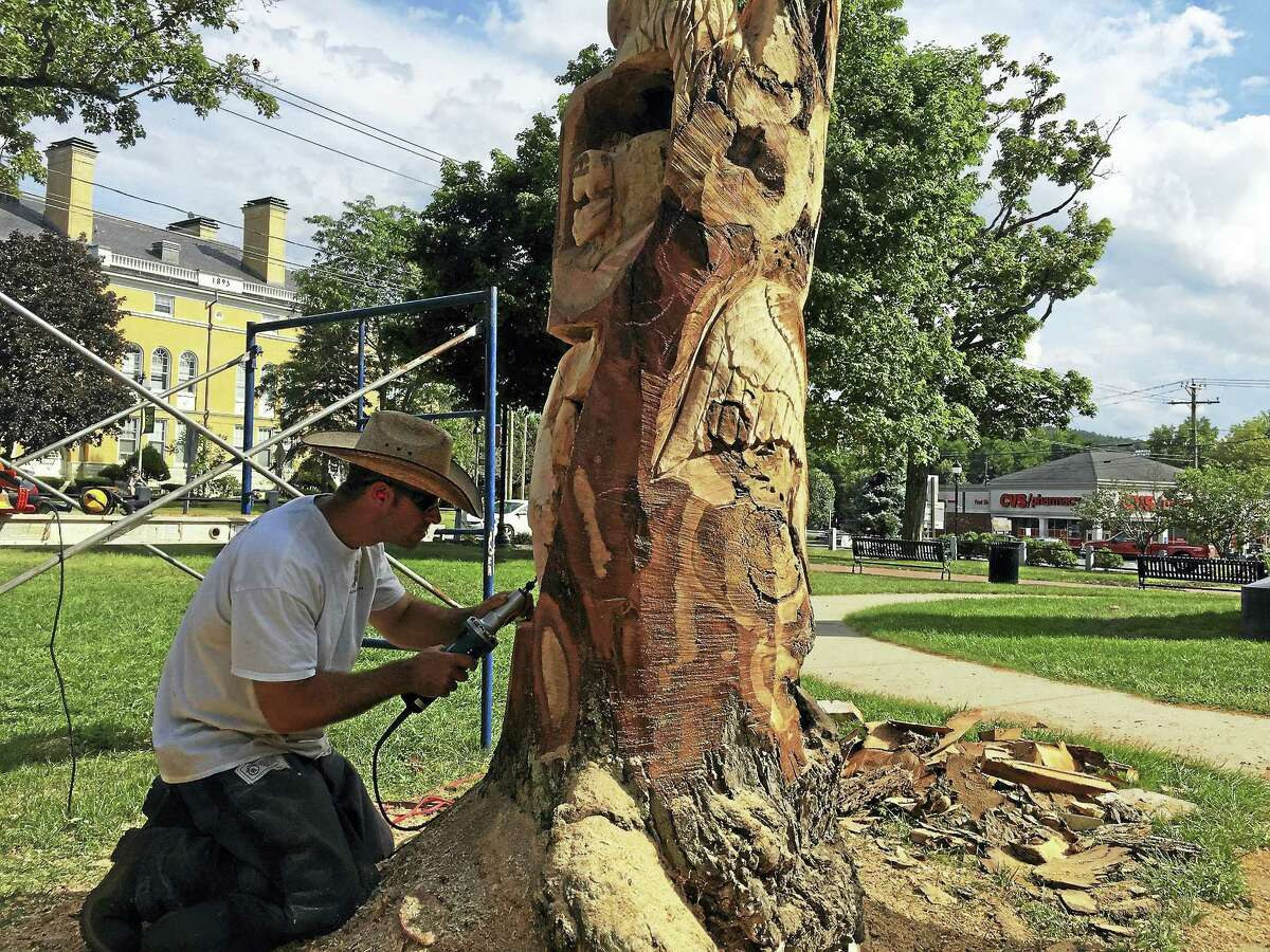 Ben Lambert - The Register Citizen Jared Welcome of JareBear Carvings works Thursday in East End Park, carving animals out of the remains of a dead tree.