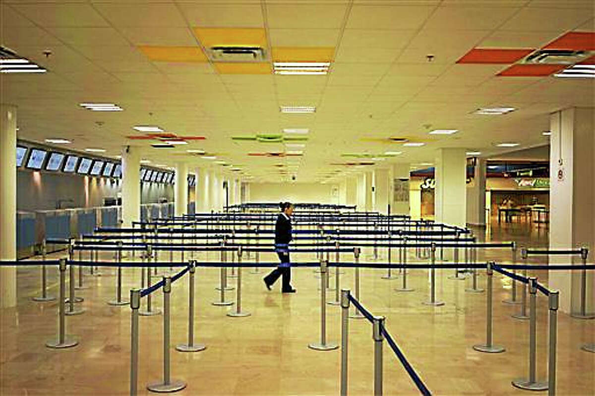 """An airline employee walks in the empty airport where all flights are canceled as Hurricane Patricia approaches the Pacific resort city of Puerto Vallarta, Mexico, Friday. Oct. 23, 2015. Patricia headed toward southwestern Mexico Friday as a monster Category 5 storm, the strongest ever in the Western Hemisphere that forecasters said could make a """"potentially catastrophic landfall"""" later in the day."""