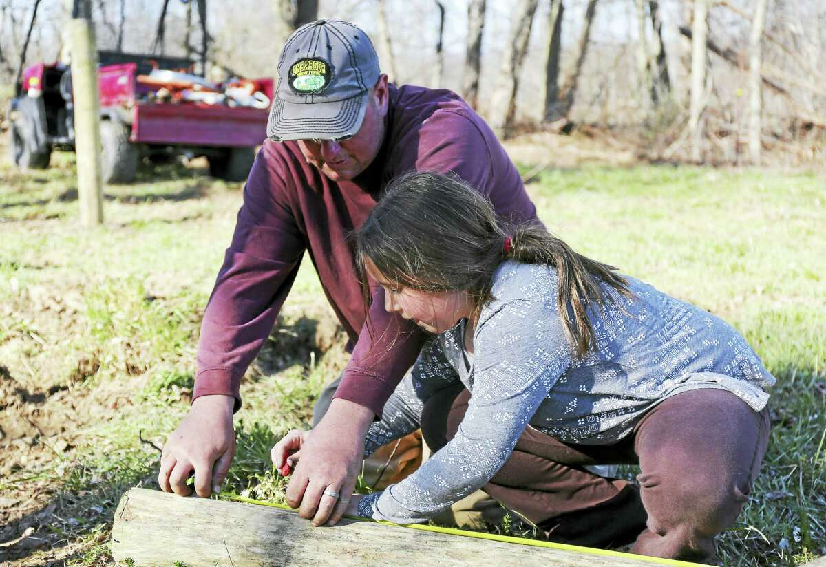 Mackenzie Maynard helps her dad Mark measure a post for the Good Hill Farm property.