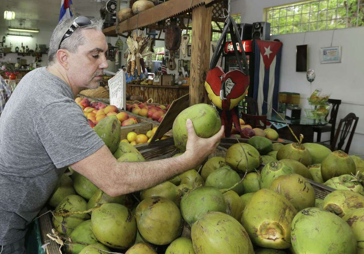 In this photo taken Tuesday, June 9, 2015, shopper Julian Fojon-Losada, of Georgia, checks a coconut at a local fruit store in the Little Havana area of Miami. The Commerce Department releases its May report on consumer spending, which accounts for 70 percent of economic activity, on Thursday, June 25, 2015. (AP Photo/Alan Diaz)