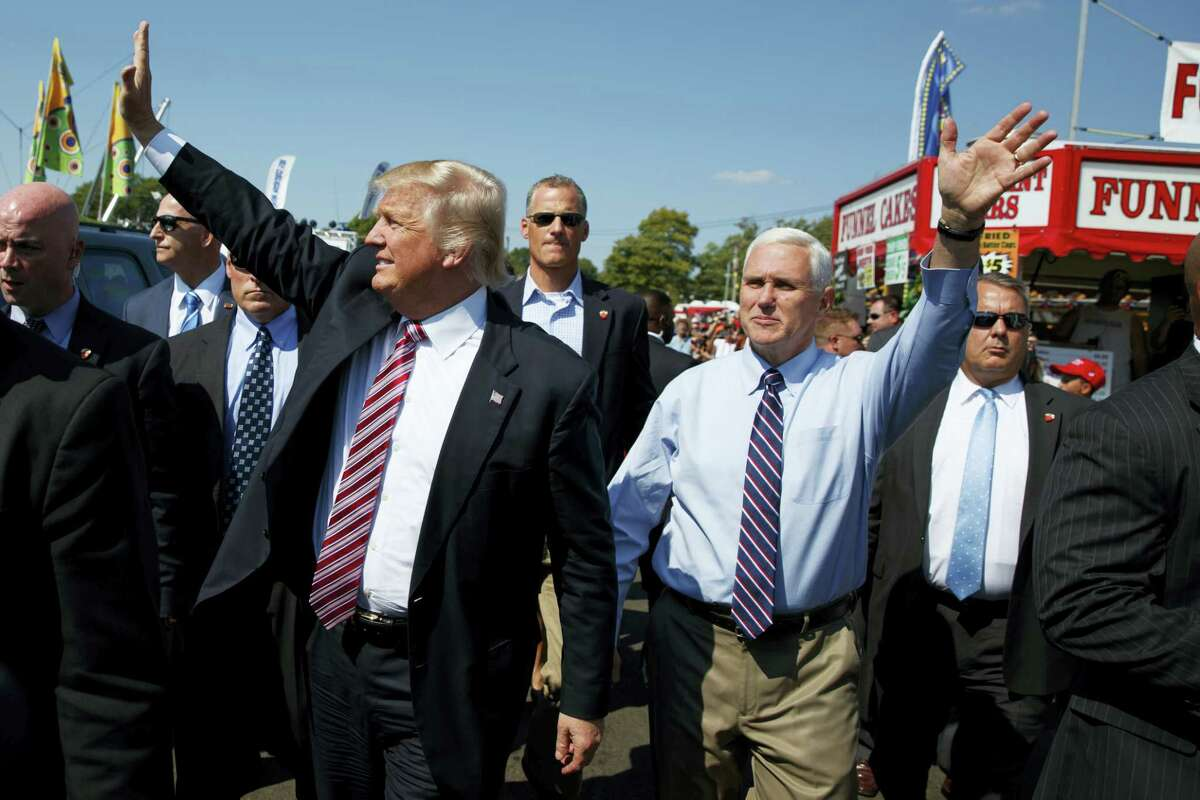 Republican presidential candidate Donald Trump, center left, waves as he walks with vice presidential candidate Gov. Mike Pence, R-Ind., center right, during a visit to the Canfield Fair on Sept. 5, 2016, in Canfield, Ohio.