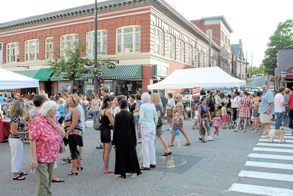 Register Citizen fil photo ¬ Crowds of people enjoy a night out at Main Street Marketplace in Torrington.