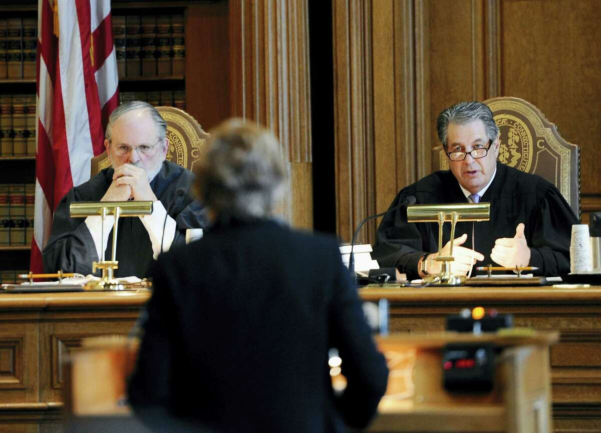 Justice Richard M. Palmer, right, asks a question of prosecutor Susan Gill, center, as Justice Peter T. Zarella, left, listens, during a hearing for Michael Skakel at the state Supreme Court, Wednesday, Feb. 24, 2016, in Hartford. State prosecutors asked the state Supreme Court on to reinstate the 2002 murder conviction against Kennedy cousin Skakel in the bludgeoning death of Martha Moxley when they were teenage neighbors in wealthy Greenwich.