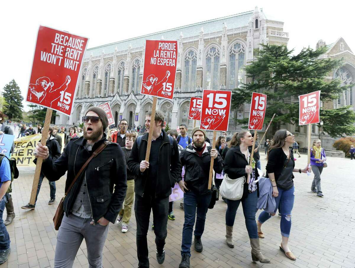 In this April 1, 2015, photo, students and other supporters protest on the University of Washington campus in Seattle, in support of raising the minimum wage for campus workers to $15 an hour.