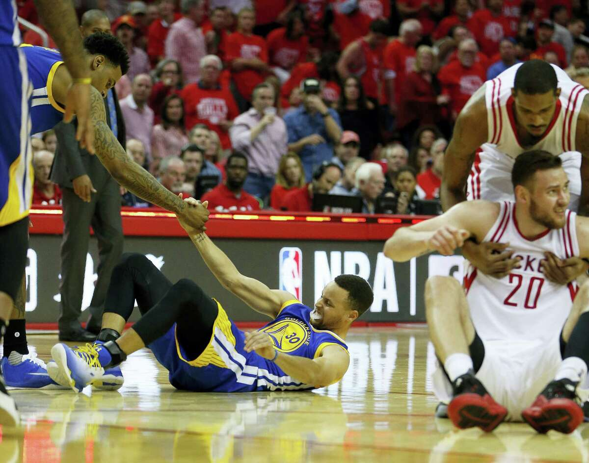 In this April 24, 2016 photo, Golden State Warriors guard Stephen Curry (30) is helped up after being injured on the final play during the first half of Game 4 in the first round of the NBA playoff series against the Houston Rockets, in Houston.