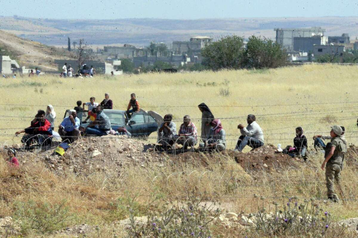 Turkish soldiers stand as people from the Syrian town of Ayn al-Arab or Kobani wait to cross into Turkey following the attacks by IS militants as seen from the Turkish side of the border in Suruc, Turkey, Thursday, June 25, 2015. Islamic State militants launched two major attacks in northern Syria on Thursday, storming government-held areas in the mostly Kurdish city of Hassakeh and pushing into Kobani, the Syrian Kurdish border town they were expelled from early this year.
