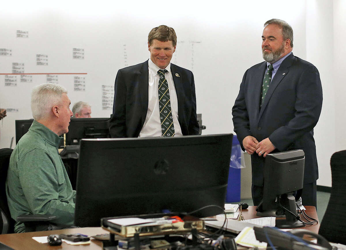 Green Bay Packers general manager Ted Thompson, left, president Mark Murphy, center, and head coach Mike McCarthy talk inside the 'war room' during the 2016 NFL draft.