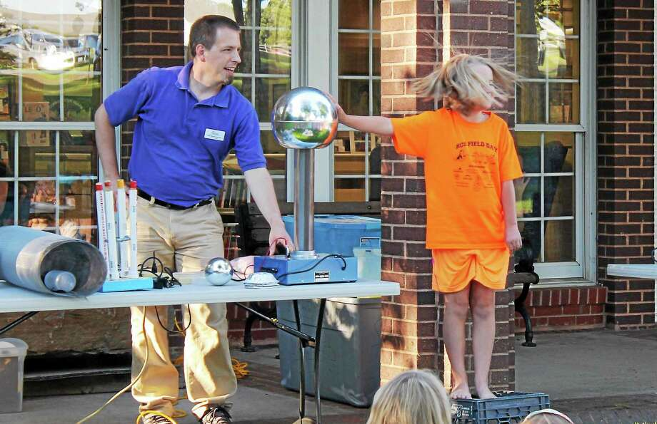 PHOTO BY JOHN NESTOR Dan Butterworth, The Childrens Museumís education program coordinator, entertained at the kickoff of the Harwinton Public Library's summer reading program Wednesday night. Highlights included making some volunteersí hair stand on end with electric currents, light tubes that glowed like light sabers thanks to a Tesla Coil and an experiment that illustrated how Franklin made the case that all houses and barns should have a lightning rod. Photo: Journal Register Co.