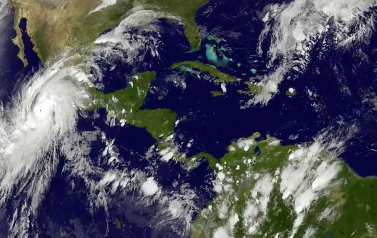 This satellite image taken at 8:45 p.m. EDT on Thursday, Oct. 22, 2015, and released by the National Oceanic and Atmospheric Administration shows Hurricane Patricia, left, moving over Mexico's central Pacific Coast. The powerful Category 4 storm bore down on Mexico's central Pacific Coast on Thursday night, for what forecasters said could be a devastating blow, as officials declared a state of emergency and handed out sandbags in preparation for flooding.