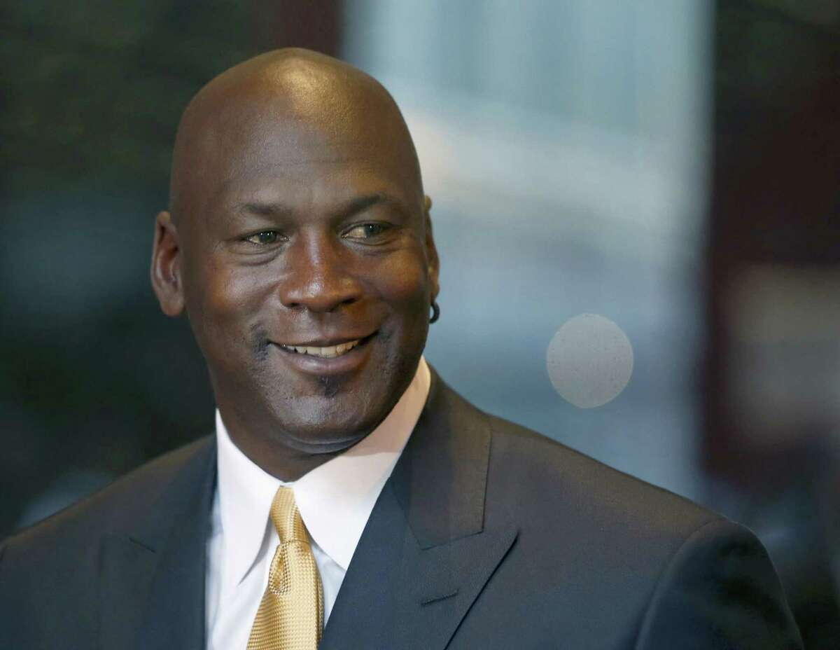 "In this Aug. 21, 2015 photo, former NBA star Michael Jordan smiles at reporters in Chicago. Nike is opening a Michael Jordan-only store in Chicago's Loop on Oct. 24, 2015. The new Jordan Brand store will sell merchandise with the trademarked Michael Jordan ""Jumpman"" silhouette. Nike also plans stores in New York, Los Angeles and Toronto featuring the former Chicago Bulls star."