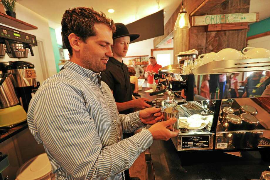 JOHN FITTS — THE REGISTER CITIZEN Giv Coffee co-owner Jeff Brooks, and Chris Bugnacki work at the Cappuccino machine at the Giv Coffee Roastery and Cafe in Canton. Photo: Journal Register Co.