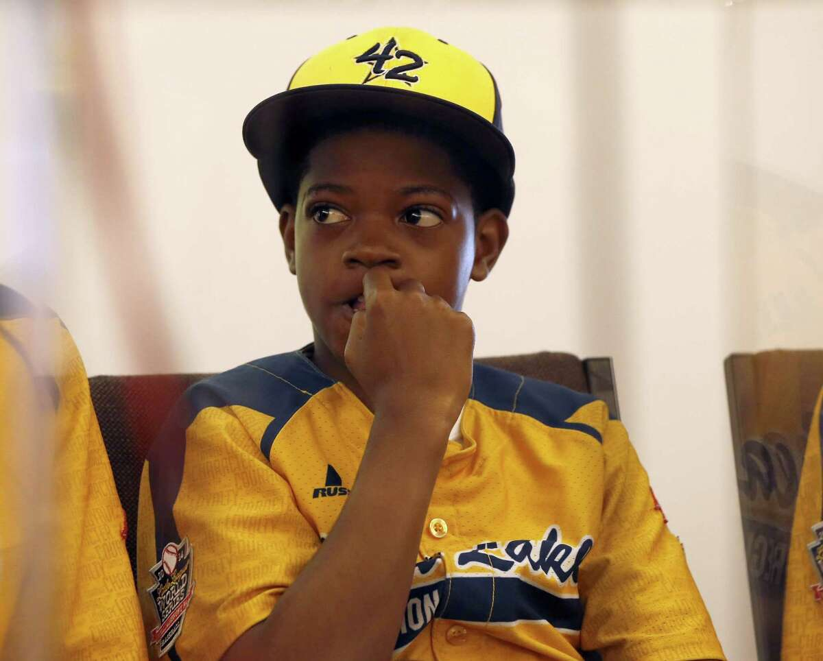 Jackie Robinson West Little League player DJ Butler listens as team attorney Victor Henderson addresses reporters at a news conference Wednesday in Chicago.