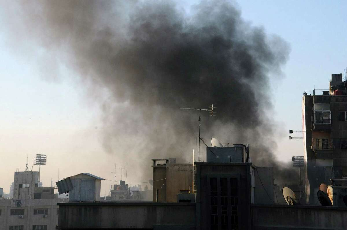 In this photo released by the Syrian official news agency SANA, smoke rises after rebels fired rockets and mortar shells that struck several parts in the capital Damascus, Syria on Feb. 5, 2015.