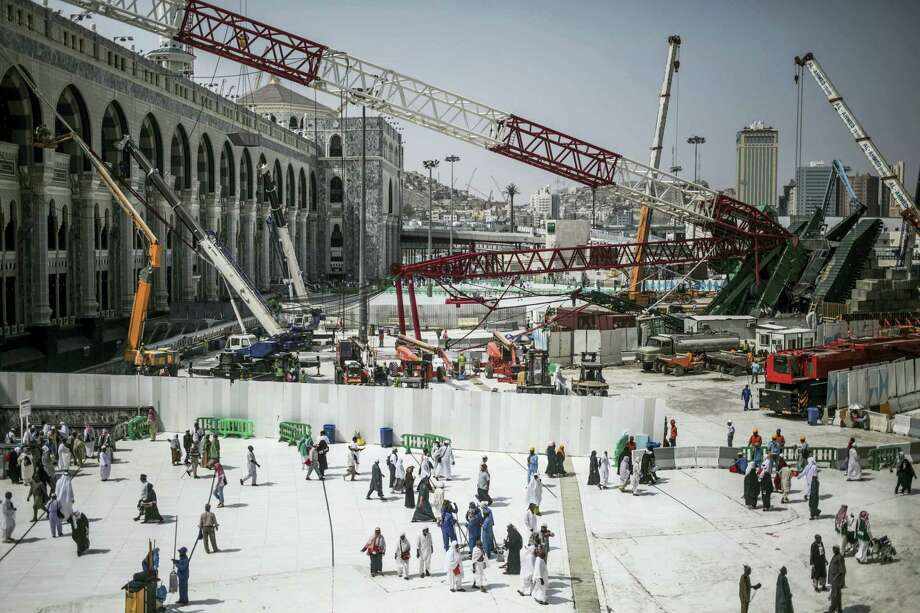 In this Tuesday, Sept. 15, 2015 photo, Muslim Pilgrims walk past the site of a crane collapse that killed over a hundred Friday at the Grand Mosque in the holy city of Mecca, Saudi Arabia. Employees at giant construction firm, the Saudi Binladin Group, have set fire to more than seven company buses to protest a reportedly large round of looming layoffs and not being paid their salaries for months. Photo: AP Photo/Mosa'ab Elshamy, File  / Copyright 2016 The Associated Press. All rights reserved. This material may not be published, broadcast, rewritten or redistribu