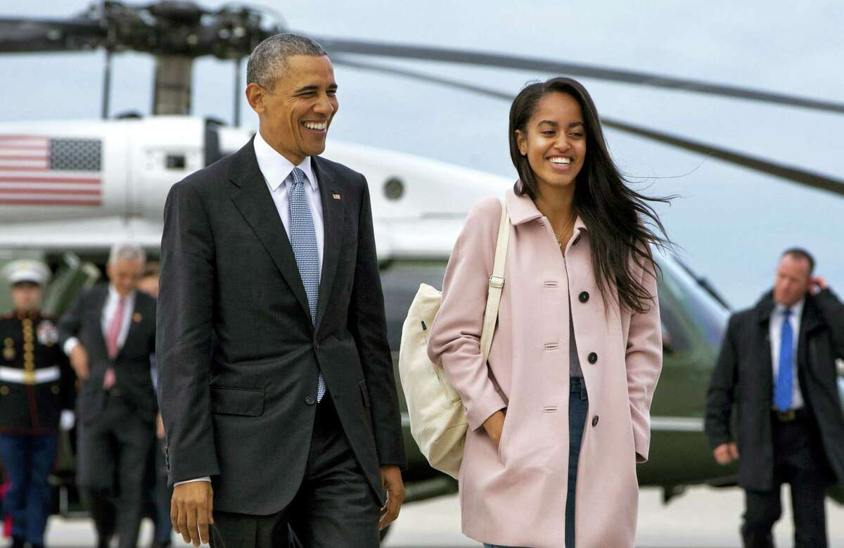 In an April 7, 2016 photo, President Barack Obama jokes with his daughter Malia Obama as they walk to board Air Force One from the Marine One helicopter, as they leave Chicago en route to Los Angeles.