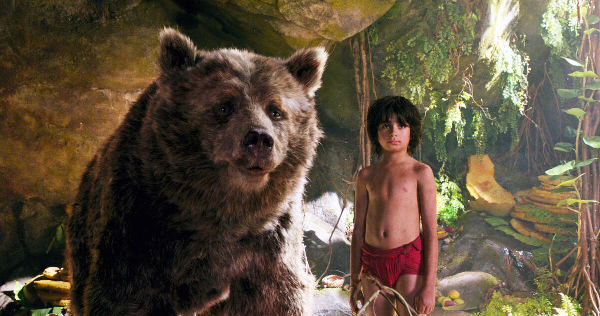 """In this image released by Disney, Mowgli, portrayed by Neel Sethi, right, and Baloo the bear, voiced by Bill Murray, appear in a scene from, """"The Jungle Book."""""""