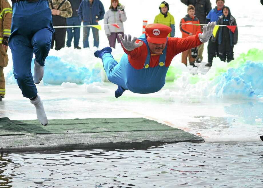 Matt Smith jumps into Highland Lake in Winsted for the annual Penguin Plunge to raise money for Special Olympics. Smith's team, Team Mario, raised more than $32,000 for the event. Photo: Register Citizen File Photo