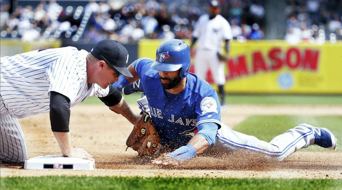 New York Yankees third baseman Chase Headley tags out Toronto's Jose Bautista out at third in the fifth inning Monday. The Yankees won 5-3.