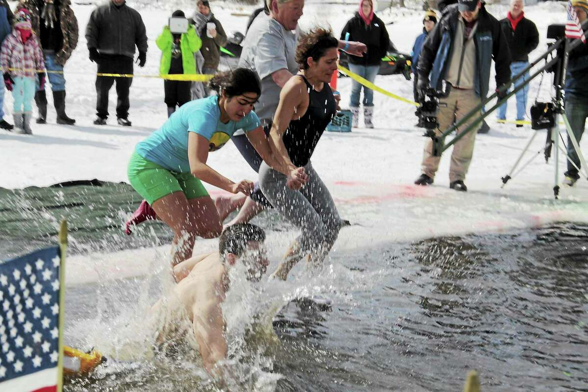 Participants jump into Highland Lake in Winsted for the annual Penguin Plunge, an event that helps raise funds for Special Olympics.