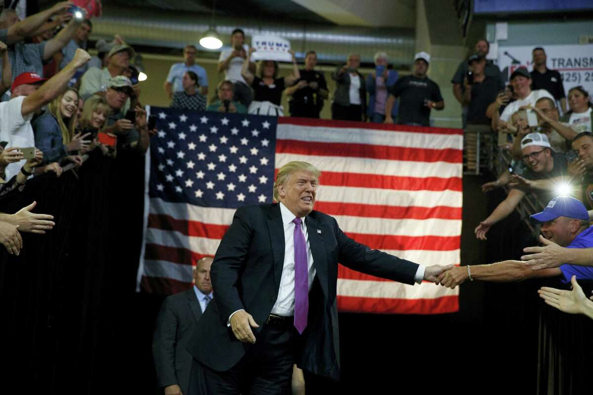 Republican presidential candidate Donald Trump shakes hands as he arrives to a campaign rally at Xfinity Arena of Everett, Tuesday, Aug. 30, 2016, in Everett, Wash. (AP Photo/Evan Vucci)