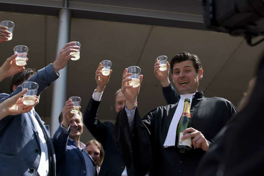 Urgenda Foundation lawyer Roger Cox, right, proposes a toast on the steps of the court house in a scene setup by TV in The Hague, Netherlands, Wednesday, June 24, 2015. A Dutch court has ordered the government to cut the country's greenhouse gas emissions by at least 25 percent by 2020 in a groundbreaking climate case that activists hope will set a worldwide precedent. The Hague District Court made the ruling Wednesday in a case brought by a sustainability organization on behalf of some 900 citizens, claiming that the the government has a duty of care to protect its citizens against looming dangers. (AP Photo/Peter Dejong) Photo: AP / AP