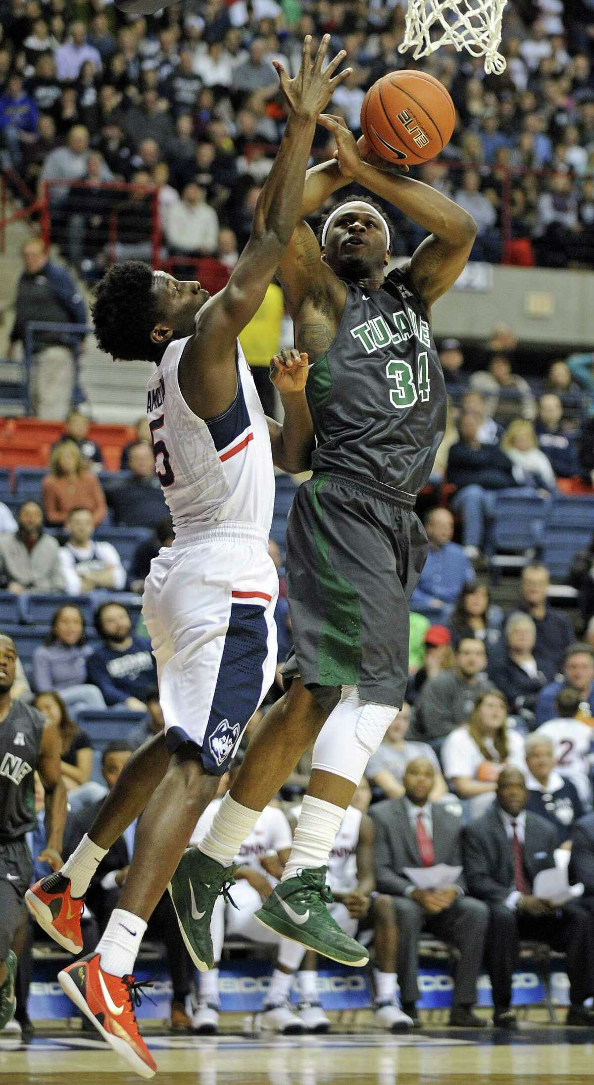 Tulane's Tre Drye, right, is fouled by UConn's Daniel Hamilton during the first half on Sunday.
