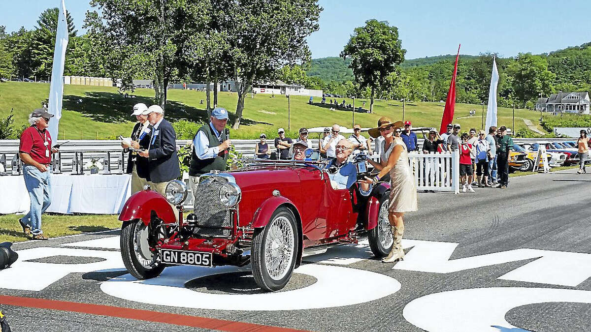 """Lime Rock Park Chairman Murray Smith emceed the awards ceremony as Nancy DePecol of Northwest Connecticut's Chamber of Congress presented an award to a vintage-car winner at the invitation-only """"Concours d'Elegance"""" show of historic cars and motorcycles along the Sam Posey Straight track at Lime Rock Park on Sunday afternoon."""
