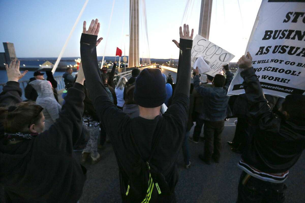 Protesters hold up their hands and signs on the cable bridge Feb. 21, 2015, during a protest stemming from the officer involved shooting death of Antonio Zambrano-Montes.