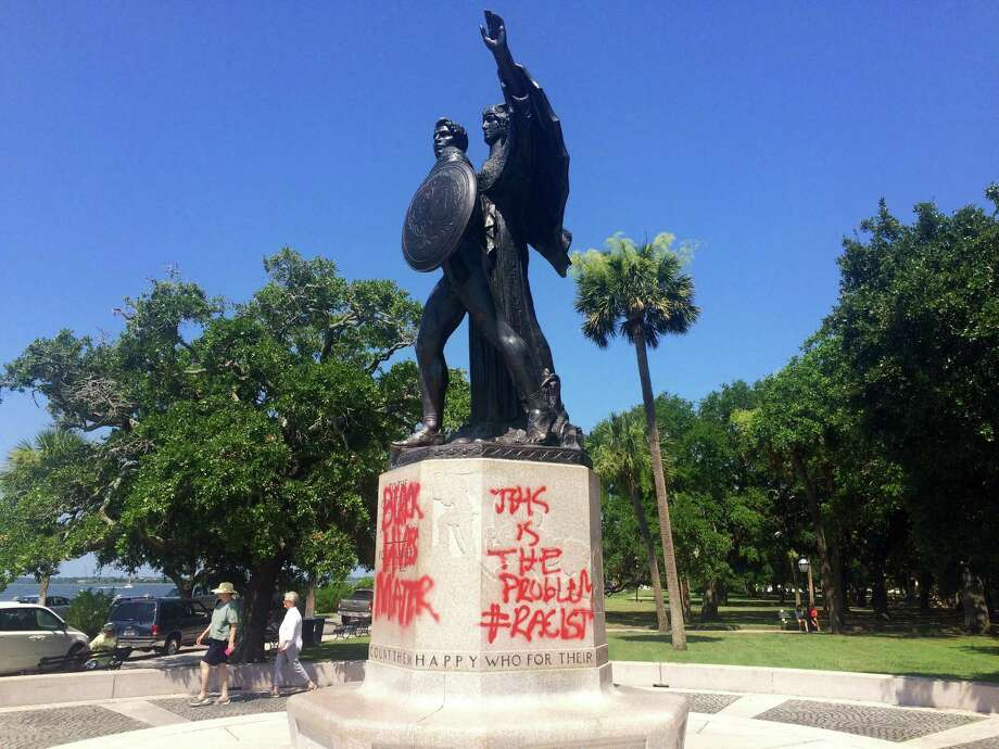 A statue memorializing the Confederacy is spray-painted several days after a shooting at a historic black church Sunday, June 21, 2015, in Charleston, S.C. Police spokesman Charles Francis said city workers used a tarp to cover up the graffiti marking the stone pedestal beneath the statue. He said he didn't know when the graffiti was spray-painted there, but said it would be cleaned off. (AP Photo/WCSC-TV, Philip Weiss) Photo: AP / WCSCTV