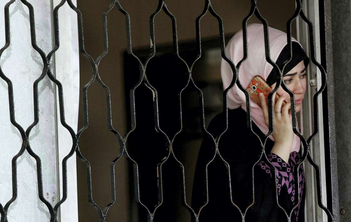 A Palestinian woman talks on her mobile phone as she waits to cross the border to the Egyptian side of Rafah crossing with Egypt, in Khan Younis City, Gaza Strip, Wednesday, June 29, 2016. Hamas says Egypt has temporarily opened its border with the Gaza Strip for five days during the holy month of Ramadan and before the upcoming of Eid al-Fitr. The Rafah border crossing, Gaza's main gateway to the outside world, will operate Wednesday until Monday.