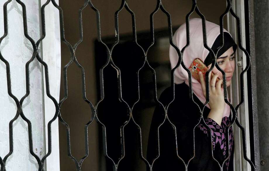 A Palestinian woman talks on her mobile phone as she waits to cross the border to the Egyptian side of Rafah crossing with Egypt, in Khan Younis City, Gaza Strip, Wednesday, June 29, 2016. Hamas says Egypt has temporarily opened its border with the Gaza Strip for five days during the holy month of Ramadan and before the upcoming of Eid al-Fitr. The Rafah border crossing, Gaza's main gateway to the outside world, will operate Wednesday until Monday. Photo: AP Photo/Adel Hana   / Copyright 2016 The Associated Press. All rights reserved. This material may not be published, broadcast, rewritten or redistribu