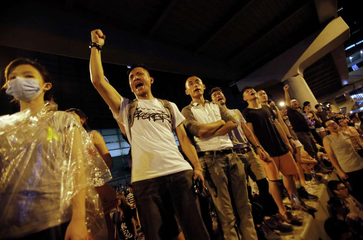 Protesters cheer on the announcement of the official occupation of streets surrounding government headquarters in Hong Kong, China, in this file photo.
