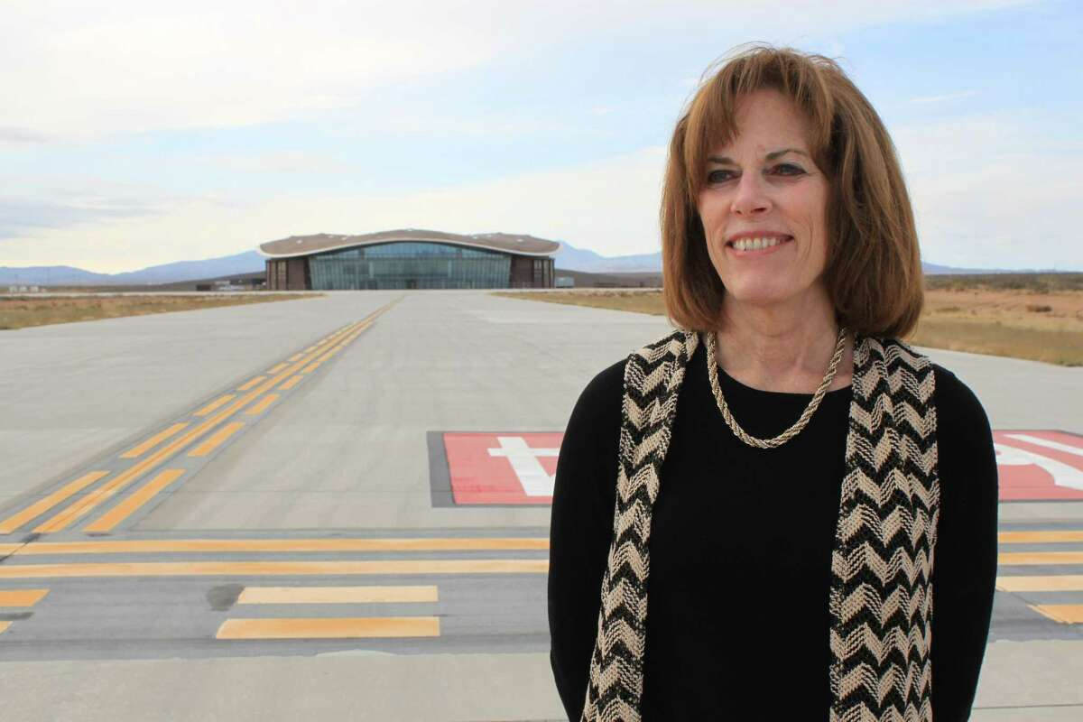 Christine Anderson, executive director of the New Mexico Spaceport Authority, poses for a photo at the end of the taxiway at Spaceport America.