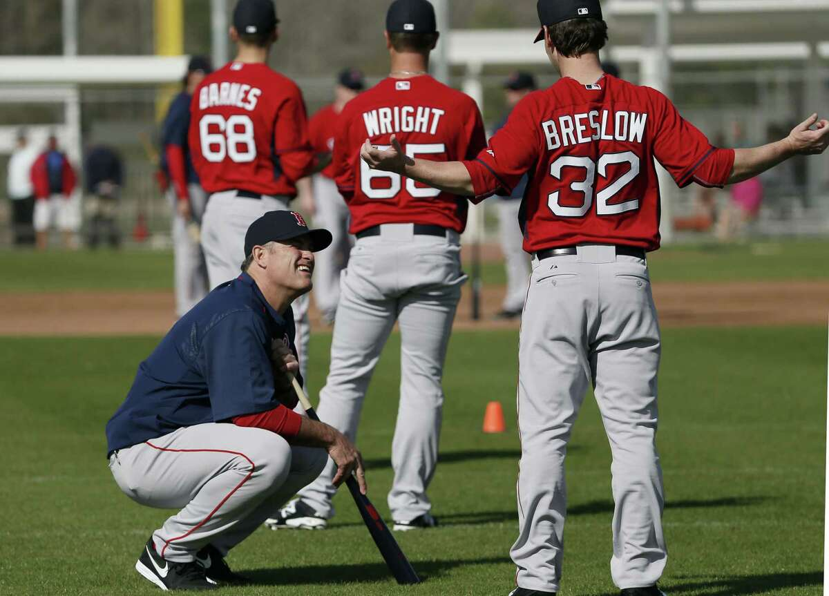 Boston Red Sox manager John Farrell, left, talks with relief pitcher Craig Breslow as the team stretches during spring training Saturday in Fort Myers Fla.